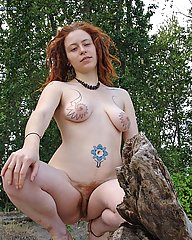 Redhead with Dreadlocks. Young hippie with amazing tattoos on her large breasts. Full red bush and pits.