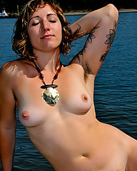 Beautiful, young, modern goddess strips at the beach. She has a full bush and fluffy armpit hair.