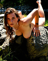Brunette hippie with large breasts and hairy bush outdoors.