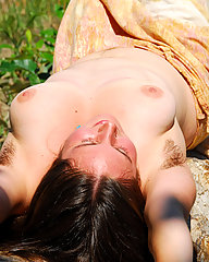 Hairy hippie girl with curvy body and large breasts posing nude with full bush.