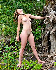 Sexy young hippie with Dreadlocks and hairy body outdoors strips and poses.